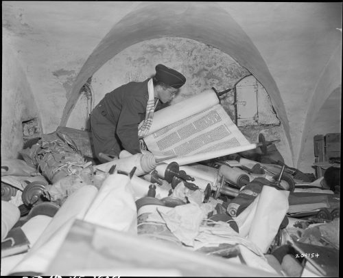Saphor Torahs Chaplain Samuel Blinder examines one of the hundreds of Saphor Torahs (sacred scrolls) part of a cache of Hebrew and Jewish books that were stolen and collected from every occupied country in Europe. 7/6/45.